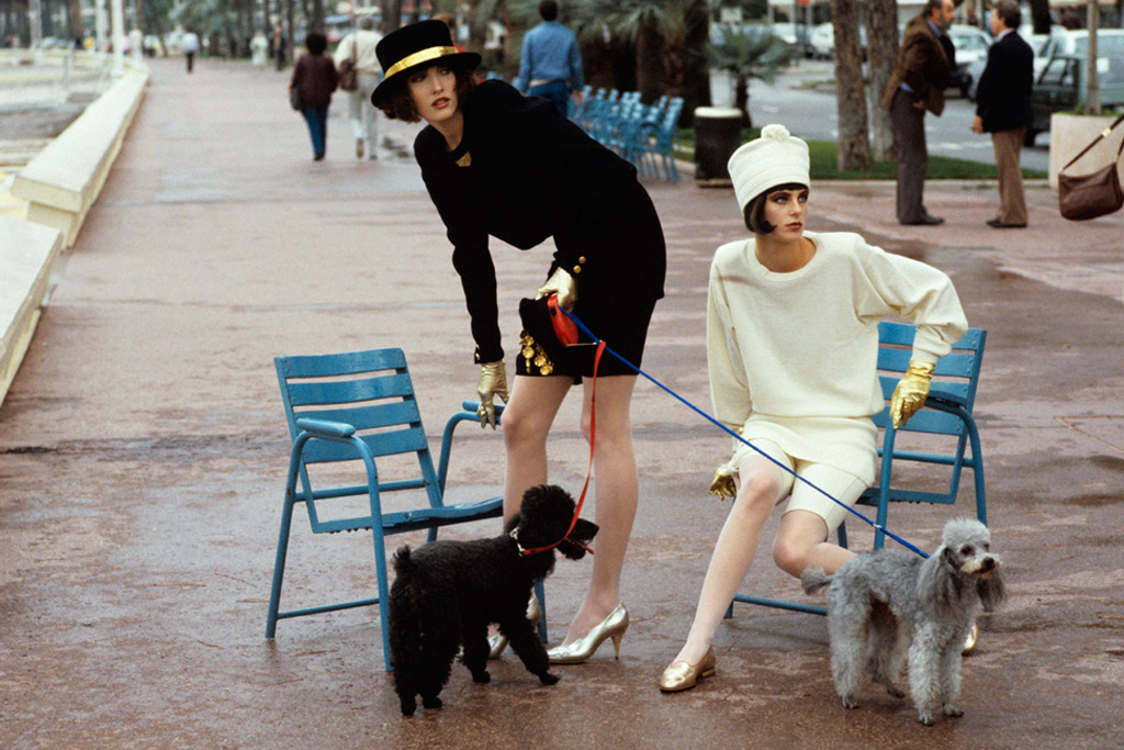 Models Tatjana and Laetitia Firmin-Didot holding two French poodles on leashes in a park; at left, both wear fashions by Sonia Rykiel. Circa January 1986.