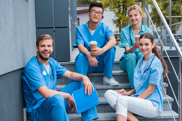 Happy Multicultural Medical Students Sitting Stairs Looking Camera — стоковое фото